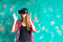 Young woman getting experience using VR-headset glasses of virtual reality much gesticulating hands Stock Photography