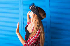 Young woman getting experience using VR-headset glasses of virtual reality much gesticulating hands Stock Image