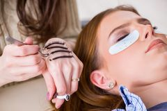 The young woman getting eyelash extension. Young woman getting eyelash extension royalty free stock images