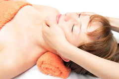 Young woman getting facial massage. Hands massaging female face at the spa Stock Photos