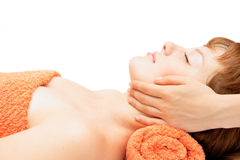 Young woman getting facial massage. Hands massaging female face at the spa Stock Photo