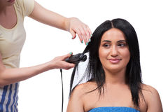 The young woman getting hair straightner isolated on white Stock Photo