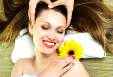Young woman getting a head massage. Beautiful happy woman getting a professional head massage Stock Photography