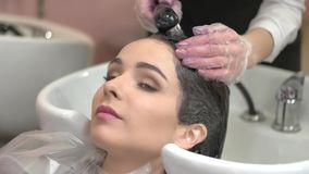 Young woman getting head washed. Beautician rinsing hair after dying stock video