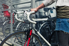Young woman getting her bike out of a bicycle shed Stock Photo