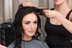 Young woman getting her hair curled by stylist at parlor. Stock Images