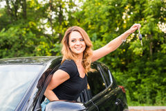 Young woman getting her key in the car. Concept of rent car or buying car. Stock Images