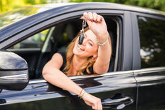 Young woman getting her key in the car. Concept of rent car or buying car Stock Photo