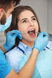 Young woman getting her teeth checked by a dentist. royalty free stock images
