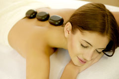 Young woman getting a hot stone massage. Portrait of an attractive young brunette woman getting a hot stone massage in cosmetics studio Stock Photo