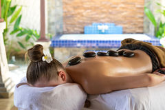 Young woman getting hot stone massage in spa salon. Beauty treat. Ment concept Stock Photography