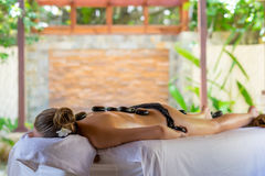 Young woman getting hot stone massage in spa salon. Beauty treat. Ment concept Royalty Free Stock Image