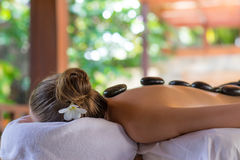 Young woman getting hot stone massage in spa salon. Beauty treat. Ment concept Stock Photo