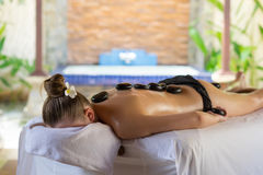 Young woman getting hot stone massage in spa salon. Beauty treat. Ment concept Royalty Free Stock Images