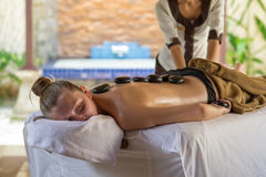 Young woman getting hot stone massage in spa salon. Beauty treat. Young women getting hot stone massage in spa salon. Beauty treatment concept Royalty Free Stock Photos