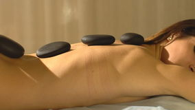 Young woman getting hot stone massage in spa salon stock video footage