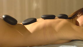 Young woman getting hot stone massage in spa salon stock footage