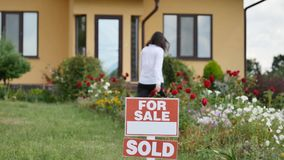 Young woman getting a key to her new house from their realtor on the door of new house background.  stock video footage