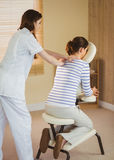 Young woman getting massage in chair. Young women getting massage in chair in therapy room royalty free stock photo
