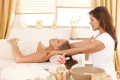 Young woman getting massage in day spa. Young woman lying on bed in day spa, getting massage Stock Photos