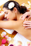 Young woman getting massage in spa salon. Stock Photos