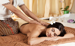 Young woman getting massage in Thai spa. Royalty Free Stock Photography