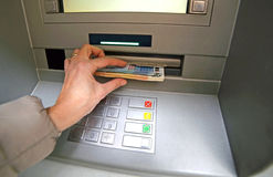 Young woman while she getting money from ATM Royalty Free Stock Images