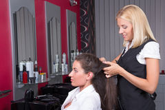 Young woman getting a new haircut by hairdresser at barbershop Royalty Free Stock Photography