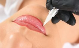 Young woman getting permanent makeup. On lips in beautician salon, closeup royalty free stock photography