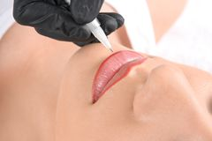 Young woman getting permanent makeup on lips in beautician salon. Closeup royalty free stock image