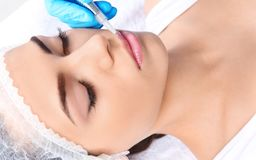 Young woman getting permanent makeup on lips. In beautician salon royalty free stock photos