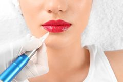 Young woman getting permanent makeup on lips. In beautician salon, closeup royalty free stock images