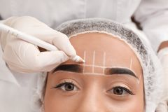 Young woman getting prepared for procedure of permanent eyebrow makeup in tattoo salon. Closeup royalty free stock image