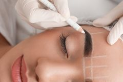 Young woman getting prepared for procedure of permanent eyebrow makeup in tattoo salon,. Closeup royalty free stock images
