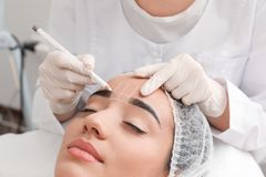 Young woman getting prepared for procedure of permanent eyebrow makeup in tattoo salon. Closeup royalty free stock images
