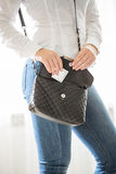 Young woman getting ready for date and putting condom in handbag royalty free stock image