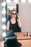 Young woman getting ready for going out. Vertical portrait of young woman with makeup getting ready for going out. Stylish girl in sunglasses sitting at mirror royalty free stock images