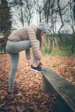Young woman getting ready for jogging. In the park Royalty Free Stock Image
