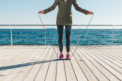 Young woman getting ready to jump on a rope. On the beach in the morning Royalty Free Stock Photos