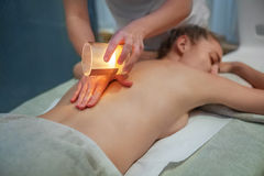 Young woman getting spa massage with massage candle Royalty Free Stock Images
