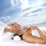 A young woman is getting spa treatment. A young and attractive woman is getting spa treatment. Image taken on a resort background with sky and water Royalty Free Stock Photos