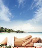Young woman getting spa treatment on the beach Stock Images
