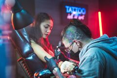 Free Young Woman Getting Tattoos In Beauty Parlor With Tattooist Working Stock Photography - 169530752