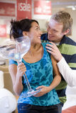 Young woman with giant cocktail glass in shop, smiling at man Royalty Free Stock Images