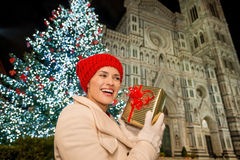 Young woman with gift box near Christmas tree in Florence, Italy. Young woman shaking gift box trying to guess what's inside near Christmas tree and Duomo in the royalty free stock photography
