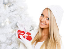Young  woman with gift. Christmas. Young happy beautiful   woman  in winter clothes with gift box stands near Christmas tree on a white background Royalty Free Stock Images