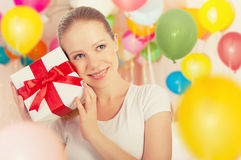 Young woman with a gift with colorful balloons Royalty Free Stock Photo