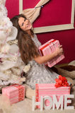 Young woman with gifts at christmas tree Royalty Free Stock Image