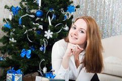 Young woman with gifts near a Christmas tree Royalty Free Stock Photography