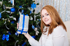 Young woman with gifts near a Christmas tree Royalty Free Stock Photos